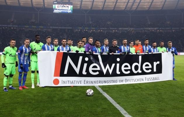 """Schalke ja Berliini Hertha mängijad enne kohtumist """"!Nie Wieder"""" kampaaniaplakatiga. Foto: Bundesliga"""